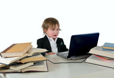 One small little girl (boy) working on computer. One small little girl (boy) wearing black suit and white shirt working on computer with books laying around on Stock Photography