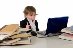 One small little girl (boy) working on computer. One small little girl (boy) wearing black suit and white shirt working on computer with books laying around on Stock Image