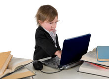One small little girl (boy) working on computer. One small little girl (boy) wearing black suit and white shirt working on computer with books laying around on Stock Images