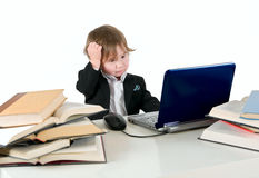 One small little girl (boy) working on computer. One small little girl (boy) wearing black suit and white shirt working on computer with books laying around on Royalty Free Stock Images
