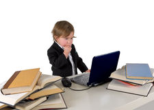 One small little girl (boy) working on computer. One small little girl (boy) wearing black suit and white shirt working on computer with books laying around on Stock Photos