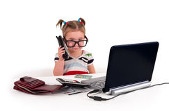 One small little girl calling phone. One small little girl wearing t-shirt, calling phone. Credit cards, gift cards, calculator, notebook on the table. Canadian Royalty Free Stock Photos