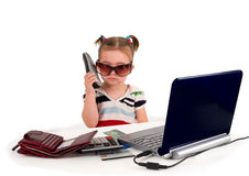 One small little girl calling phone. One small little girl wearing t-shirt. Phone, credit cards, gift cards, calculator, notebook on the table. Candian Stock Photo