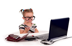 One small little girl calling phone. Sad. One small little girl wearing t-shirt. Sad. Phone, credit cards, gift cards, calculator, notebook on the table Stock Photography