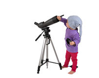 One small little girl cleaning spotting scope with lens brush. One small little girl cleaning spotting scope on tripod with hand air blower and lens brush Royalty Free Stock Images