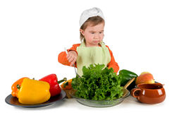 One small little girl cooking. One small little girl preparing raw fruits and vegetables for cooking. Isolated objects Royalty Free Stock Images