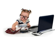 One small little girl with credit cards. One small little girl wearing t-shirt with stripes, calling phone, credit cards, calculator, notebook are on the table Stock Photography