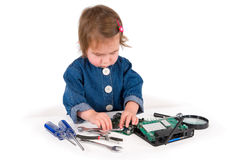 One small little girl fixing router or modem or PCB. One small little girl with set of wrench, screwdrivers, magnifying loupe repairs router or modem or PCB Royalty Free Stock Image
