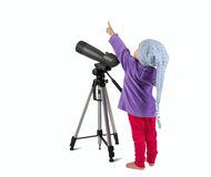 One small little girl looking through spotting scope and pointin. One small little girl looking through spotting scope on tripod and pointing up. Isolated object Royalty Free Stock Photography