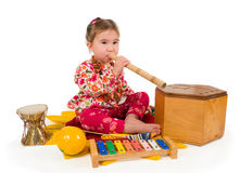 One small little girl playing music. One small little girl playing on drum, flute, maraca, xylophone. Isolated onject Stock Photography