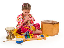 One small little girl playing music. One small little girl playing on drum, flute, maraca, xylophone. Isolated onject Royalty Free Stock Photo