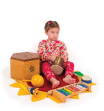 One small little girl playing music. One small little girl playing on drum, flute, maraca, xylophone. Isolated onject Royalty Free Stock Images