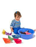 One small little girl playing with origami paper ship Royalty Free Stock Photos