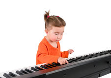 One small little girl playing piano. One small little girl learning to play piano. Isolated objects Royalty Free Stock Image