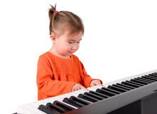 One small little girl playing piano. One small little girl learning to play piano. Isolated objects Royalty Free Stock Photography