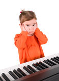 One small little girl playing piano. One small little girl learning to play piano. Isolated objects Stock Photo