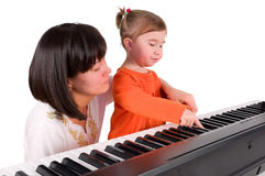 One small little girl playing piano. One small little girl learning to play piano with the teacher. Isolated objects Royalty Free Stock Photos