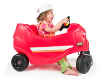 One small little girl playing with toy car. One small little girl wearing white cap, riding and playing with red toy car Royalty Free Stock Photos