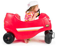 One small little girl playing with toy car. One small little girl wearing white cap, riding and playing with red toy car Royalty Free Stock Photo