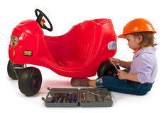 One small little girl repairing toy car. One small little girl wearing hard cap, boots, repairing toy red car. Isolated objects Royalty Free Stock Photography