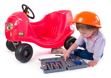 One small little girl repairing toy car. One small little girl wearing hard cap, boots, repairing toy red car. Isolated objects Royalty Free Stock Images