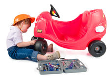 One small little girl repairing toy car. One small little girl wearing hard cap, boots, repairing toy red car. Isolated objects Stock Photo