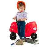 One small little girl repairing toy car. One small little girl wearing hard cap, boots, repairing toy red car. Isolated objects Royalty Free Stock Photos