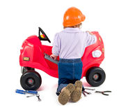 One small little girl repairing toy car. One small little girl wearing hard cap, boots, repairing toy red car. Isolated objects Stock Images
