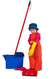 One small little girl cleaning with mop. One small little girl wearing orange apron, red t-shirt, blue hat and yellow high boots, cleaning with red mop, red Stock Image