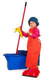 One small little girl cleaning with mop. One small little girl wearing orange apron, red t-shirt, blue hat and yellow high boots, cleaning with red mop, red Stock Photography