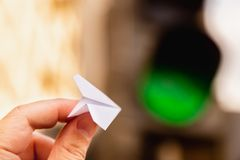 One small paper airplane in hand against a traffic light background with a glowing green signal. Permission to fly. Takeoff. Is approved and allowed. Horizontal Stock Photo