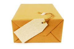 One small parcel or package with blank manila label isolated on white, end view Stock Image