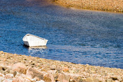 One small rowboat. A small white rowboat floating in a seacoast cove or inlet at low tide Stock Photography