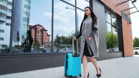 Cute 20s model is walking with a suitcase closeup. One smiling lady carry on stylish blue color airplane bag hold the valise handle outdoor. Beautiful manager go stock footage