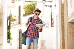 One smiling man walking in town with map and bag Stock Image