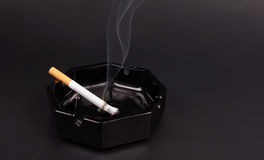 One smoking cigarette in an ashtray Stock Images