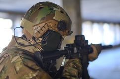 One soldier in combat gear aiming. One soldier in urban building with M4 guns and multicam gear Stock Images