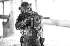 One soldier in combat gear black and white. One soldier in urban building with M4 guns and multicam gear Stock Image