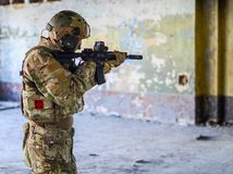 One soldier in combat gear. One soldier in urban building with M4 guns and multicam gear Royalty Free Stock Photos