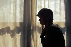 One soldier silhouette. By the window Stock Photos