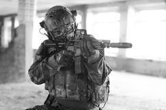 One soldier in combat gear. black and white. One soldier in urban building with M4 gun and multicam gear. black and white Stock Image