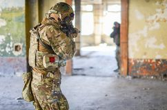 One soldier in combat gear aim at the enemy. One soldier in urban building with M4 guns and multicam gear aim at the enemy Royalty Free Stock Photos