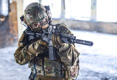 One soldier in combat gear. One soldier in urban building with M4 guns and multicam gear Royalty Free Stock Image