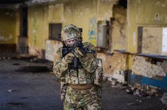 One soldier in combat gear. One soldier in urban building with M4 guns and multicam gear Royalty Free Stock Photo