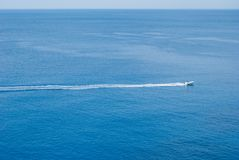 Single white motor boat with long trail behind royalty free stock photography
