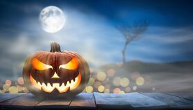 One spooky halloween pumpkin, Jack O Lantern, with an evil face and eyes on a wooden bench, table