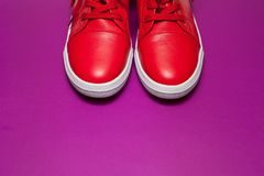 One sport red sneakers on purple background. One sport red leather sneakers on purple background royalty free stock photos