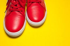 One sport red sneakers on yellow background. One sport red leather sneakers on yellow background royalty free stock photos