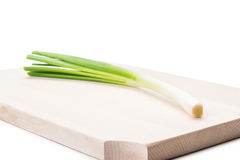 One spring onion on a wooden plate Royalty Free Stock Photo