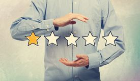 One Star Rating with businessman. On a soft colored wall stock photos